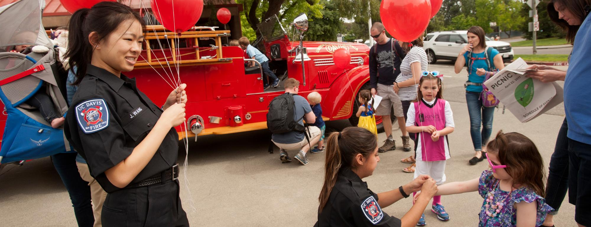 Student EMT gives child balloons at Picnic Day