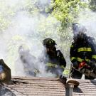 UC Davis Firefighters opening a vent hole in the roof of a home on fire.