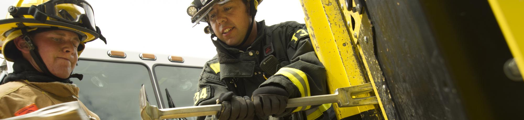 A UC Davis student firefighter learns how to force open a door from a career firefighter.